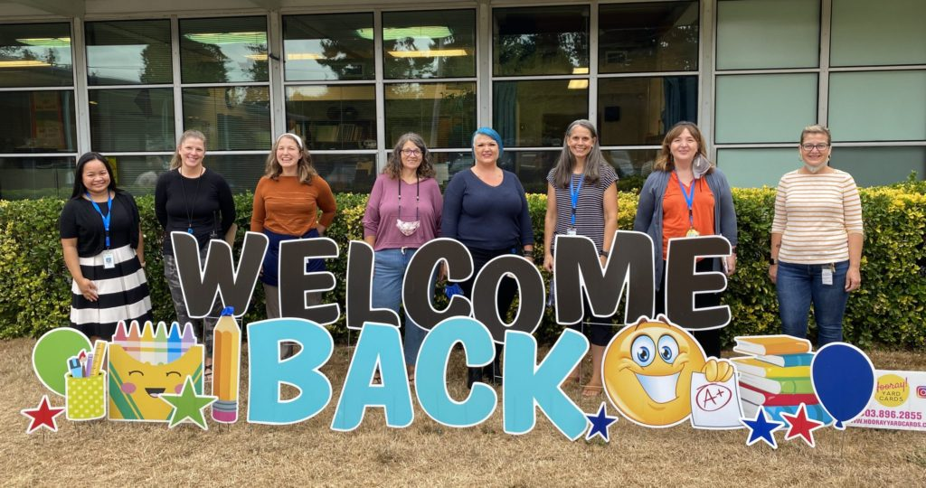 GP staff members with a welcome back cut out sign on GP lawn